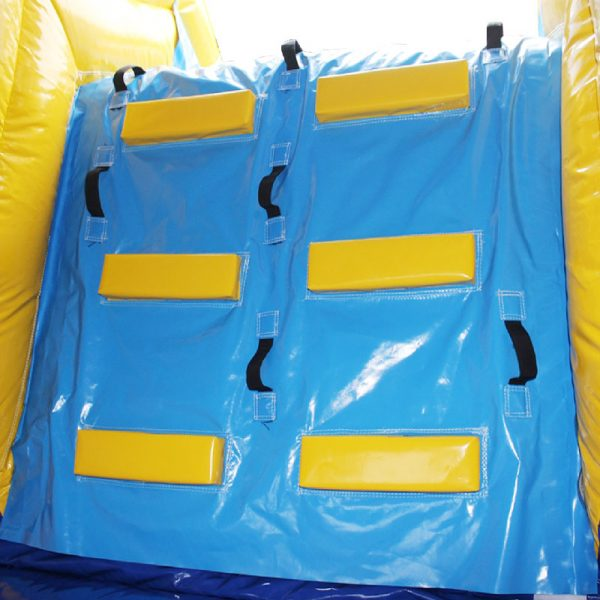 Closeup of a bouncy castle climbing wall leading to the slide. Featuring yellow steps and black handles.